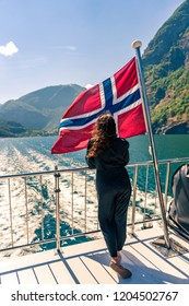 Leaving Flam port in Norway. Young woman watching coastline is getting farer  from the aft deck of fjord cruise ship. Standing close to Norwegian flag