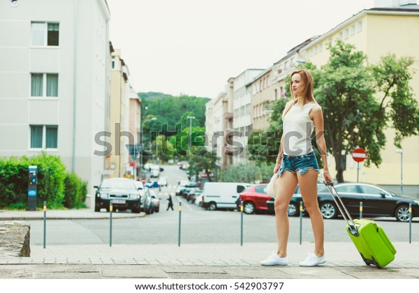Leaving and new beginnings. Young blonde woman with luggage green suitcase move out from family house. Female student looking for flat apartment in big city.