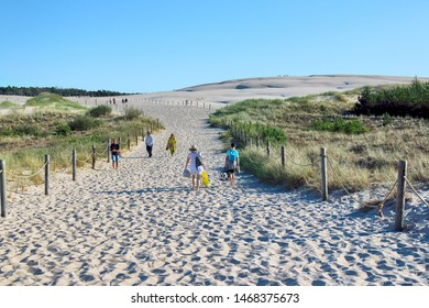 LEBA, POLAND - JULY 25, 2019: Slowinski National Park is situated on the Baltic Sea coast, near Leba, Poland. Desert landscape with the largest moving sand dunes in Europe. Hot day with clear sky.