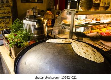 Lebanese bread on the hot saj / Kitchen of the lebanese street restaurant - lebanese flat bread (marqooq) on the the hot saj (wok-like piece of hot metal)