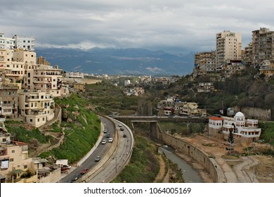 Lebanese city life. City centre with condominiums and a hill, car on the street and mountains at the background.