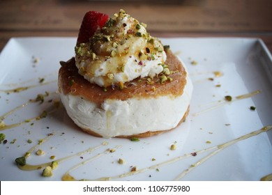 A Lebanese dessert made of ashta and vanilla ice cream with pistachios and drizzled with honey.