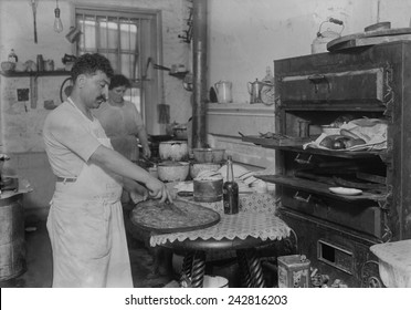 Lebanese-Syrian immigrant pastry cook cutting into a phyllo dough sweet made in the rustic kitchen of in a New York City ethnic restaurant. Ca. 1910.