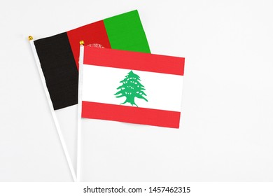Lebanon and Afghanistan stick flags on white background. High quality fabric, miniature national flag. Peaceful global concept.White floor for copy space.