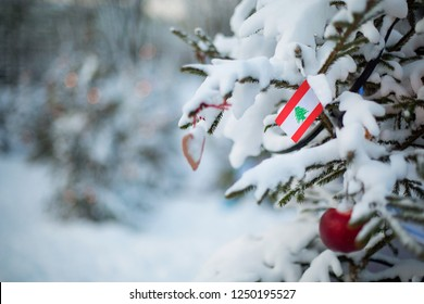 Lebanon flag. Christmas background outdoor. Xmas tree covered with snow and decorations and a national flag. Christmas and New Year holiday greeting card.