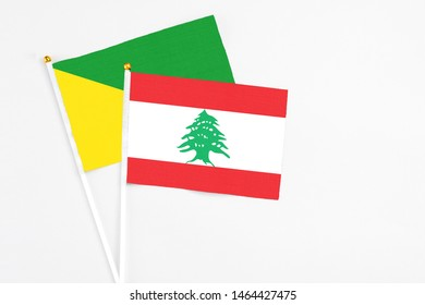 Lebanon and French Guiana stick flags on white background. High quality fabric, miniature national flag. Peaceful global concept.White floor for copy space.