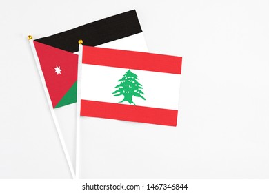 Lebanon and Jordan stick flags on white background. High quality fabric, miniature national flag. Peaceful global concept.White floor for copy space.