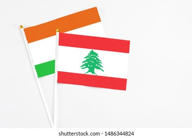 Lebanon and Niger stick flags on white background. High quality fabric, miniature national flag. Peaceful global concept.White floor for copy space.