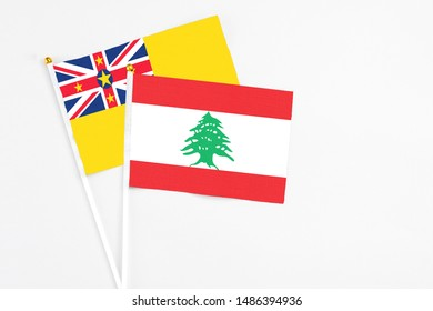 Lebanon and Niue stick flags on white background. High quality fabric, miniature national flag. Peaceful global concept.White floor for copy space.