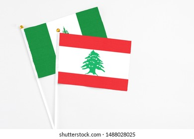 Lebanon and Norfolk Island stick flags on white background. High quality fabric, miniature national flag. Peaceful global concept.White floor for copy space.