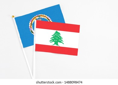 Lebanon and Northern Mariana Islands stick flags on white background. High quality fabric, miniature national flag. Peaceful global concept.White floor for copy space.