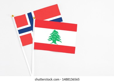 Lebanon and Norway stick flags on white background. High quality fabric, miniature national flag. Peaceful global concept.White floor for copy space.