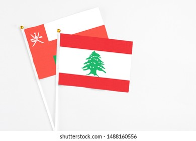 Lebanon and Oman stick flags on white background. High quality fabric, miniature national flag. Peaceful global concept.White floor for copy space.