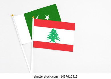 Lebanon and Pakistan stick flags on white background. High quality fabric, miniature national flag. Peaceful global concept.White floor for copy space.