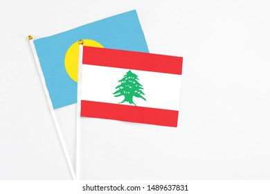 Lebanon and Palau stick flags on white background. High quality fabric, miniature national flag. Peaceful global concept.White floor for copy space.
