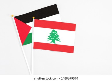 Lebanon and Palestine stick flags on white background. High quality fabric, miniature national flag. Peaceful global concept.White floor for copy space.