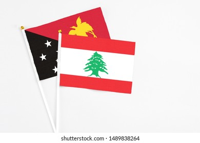Lebanon and Papua New Guinea stick flags on white background. High quality fabric, miniature national flag. Peaceful global concept.White floor for copy space.