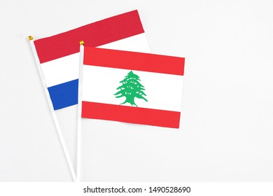 Lebanon and Paraguay stick flags on white background. High quality fabric, miniature national flag. Peaceful global concept.White floor for copy space.