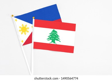 Lebanon and Philippines stick flags on white background. High quality fabric, miniature national flag. Peaceful global concept.White floor for copy space.