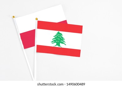 Lebanon and Poland stick flags on white background. High quality fabric, miniature national flag. Peaceful global concept.White floor for copy space.