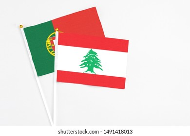Lebanon and Portugal stick flags on white background. High quality fabric, miniature national flag. Peaceful global concept.White floor for copy space.
