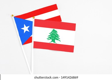 Lebanon and Puerto Rico stick flags on white background. High quality fabric, miniature national flag. Peaceful global concept.White floor for copy space.