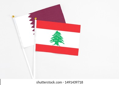 Lebanon and Qatar stick flags on white background. High quality fabric, miniature national flag. Peaceful global concept.White floor for copy space.