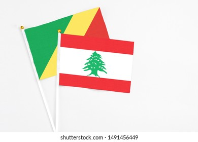 Lebanon and Republic Of The Congo stick flags on white background. High quality fabric, miniature national flag. Peaceful global concept.White floor for copy space.