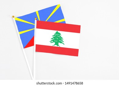 Lebanon and Reunion stick flags on white background. High quality fabric, miniature national flag. Peaceful global concept.White floor for copy space.