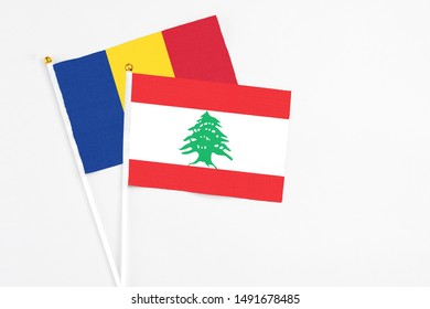 Lebanon and Romania stick flags on white background. High quality fabric, miniature national flag. Peaceful global concept.White floor for copy space.