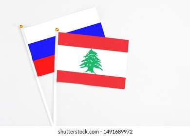 Lebanon and Russia stick flags on white background. High quality fabric, miniature national flag. Peaceful global concept.White floor for copy space.