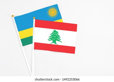 Lebanon and Rwanda stick flags on white background. High quality fabric, miniature national flag. Peaceful global concept.White floor for copy space.