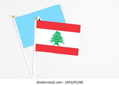 Lebanon and Saint Lucia stick flags on white background. High quality fabric, miniature national flag. Peaceful global concept.White floor for copy space.