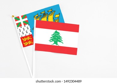 Lebanon and Saint Pierre And Miquelon stick flags on white background. High quality fabric, miniature national flag. Peaceful global concept.White floor for copy space.