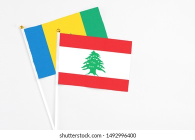 Lebanon and Saint Vincent And The Grenadines stick flags on white background. High quality fabric, miniature national flag. Peaceful global concept.White floor for copy space.