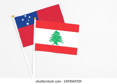 Lebanon and Samoa stick flags on white background. High quality fabric, miniature national flag. Peaceful global concept.White floor for copy space.