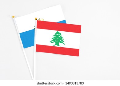 Lebanon and San Marino stick flags on white background. High quality fabric, miniature national flag. Peaceful global concept.White floor for copy space.