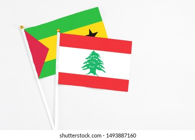 Lebanon and Sao Tome And Principe stick flags on white background. High quality fabric, miniature national flag. Peaceful global concept.White floor for copy space.