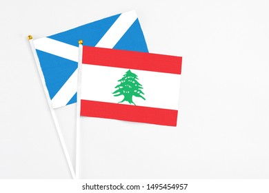 Lebanon and Scotland stick flags on white background. High quality fabric, miniature national flag. Peaceful global concept.White floor for copy space.