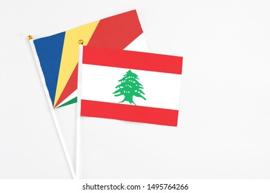 Lebanon and Seychelles stick flags on white background. High quality fabric, miniature national flag. Peaceful global concept.White floor for copy space.v