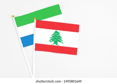 Lebanon and Sierra Leone stick flags on white background. High quality fabric, miniature national flag. Peaceful global concept.White floor for copy space.