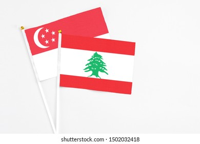 Lebanon and Singapore stick flags on white background. High quality fabric, miniature national flag. Peaceful global concept.White floor for copy space.