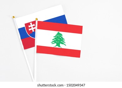 Lebanon and Slovakia stick flags on white background. High quality fabric, miniature national flag. Peaceful global concept.White floor for copy space.