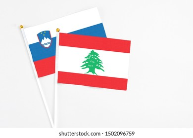 Lebanon and Slovenia stick flags on white background. High quality fabric, miniature national flag. Peaceful global concept.White floor for copy space.