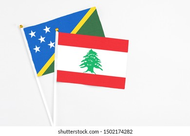 Lebanon and Solomon Islands stick flags on white background. High quality fabric, miniature national flag. Peaceful global concept.White floor for copy space.