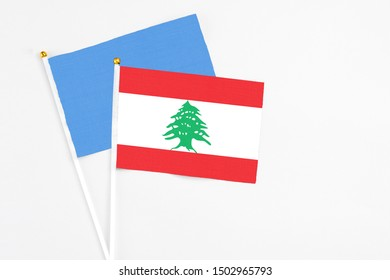 Lebanon and Somalia stick flags on white background. High quality fabric, miniature national flag. Peaceful global concept.White floor for copy space.