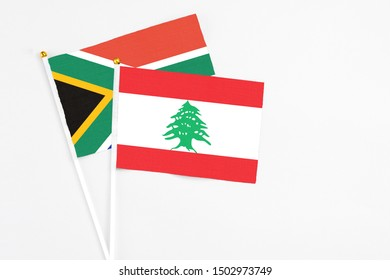 Lebanon and South Africa stick flags on white background. High quality fabric, miniature national flag. Peaceful global concept.White floor for copy space.
