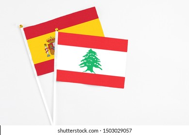 Lebanon and Spain stick flags on white background. High quality fabric, miniature national flag. Peaceful global concept.White floor for copy space.