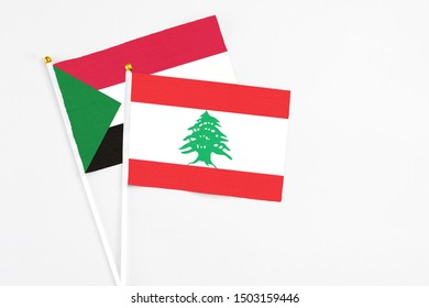 Lebanon and Sudan stick flags on white background. High quality fabric, miniature national flag. Peaceful global concept.White floor for copy space.