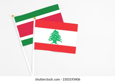 Lebanon and Suriname stick flags on white background. High quality fabric, miniature national flag. Peaceful global concept.White floor for copy space.